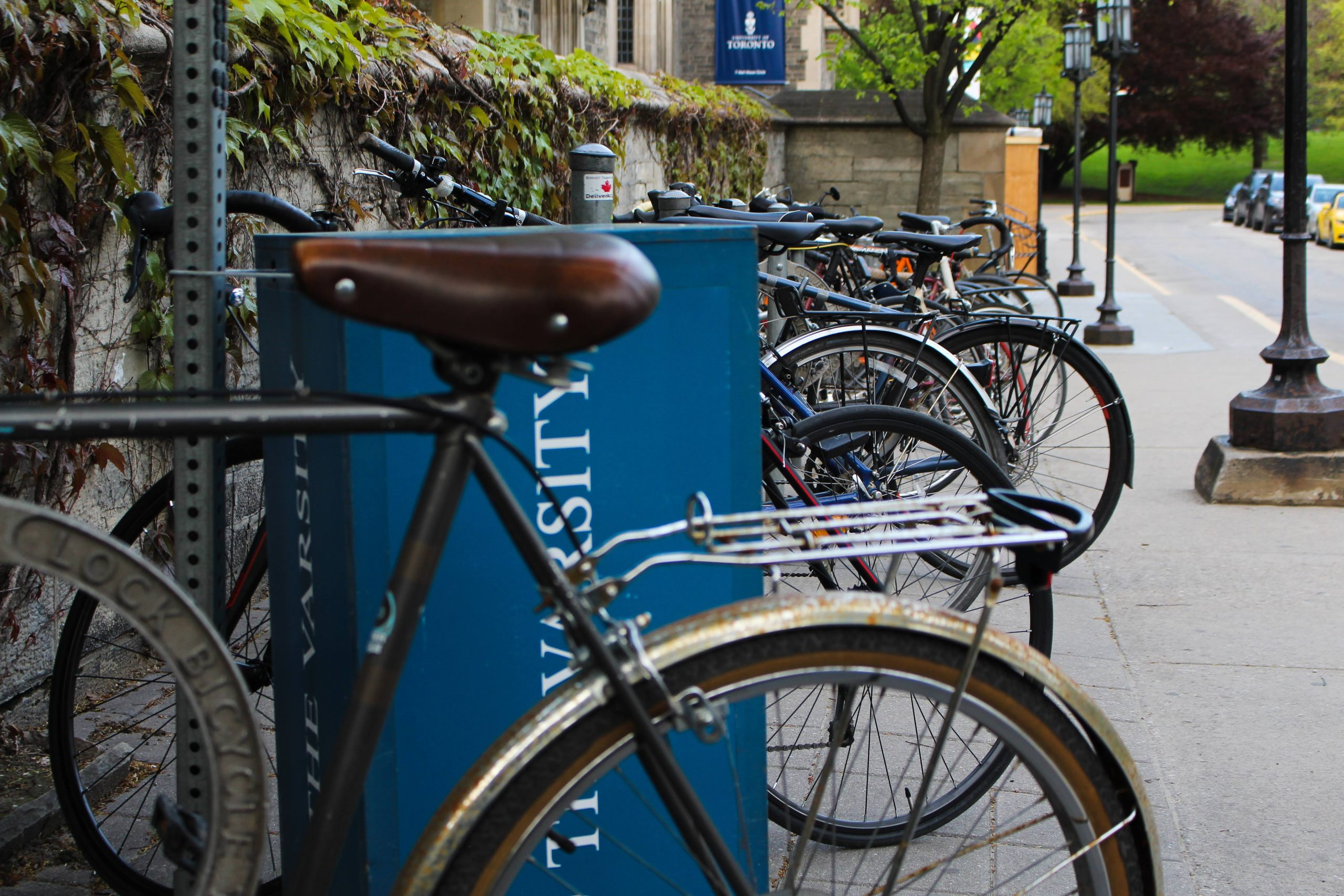 A row of bikes parked in a bike rack outside of Hart House